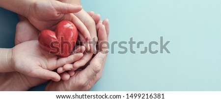 adult and child hands holding red heart on aqua background, heart health, donation, CSR, wellbeing, world heart day, world health day, family day, fair trade, foster home concept, organ donor day #1499216381