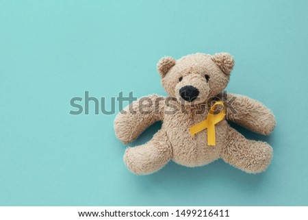 Children soft toy brown bear with yellow gold ribbon, Childhood cancer awareness Royalty-Free Stock Photo #1499216411