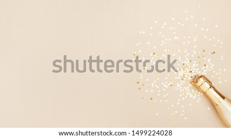 Champagne bottle with confetti stars on golden festive background. Christmas, birthday or wedding concept. Flat lay. #1499224028