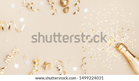 Champagne bottle with confetti stars, holiday decoration and party streamers on gold festive background. Christmas, birthday or wedding concept. Flat lay. #1499224031