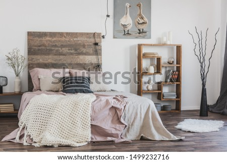 Beige, knit blanket on a pink bed with wooden bedhead in rustic bedroom interior for a woman #1499232716