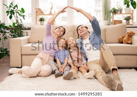 Young parents keeping their hands close forming roof over their two little kids while sitting on the floor of living-room #1499295281