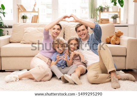 Happy parents and two adorable siblings sitting on the floor by couch in front of camera and making heart shape with fingers #1499295290