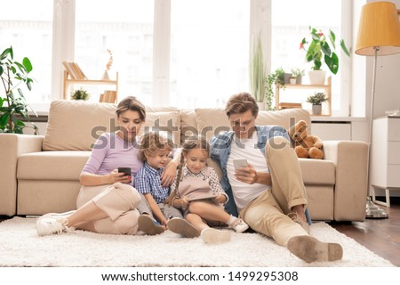 Modern family of young couple and two kids sitting on the floor by couch and using their mobile gadgets in living-room #1499295308