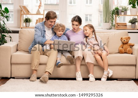 Young family of four with laptop surfing in the net while choosing movie or cartoons to watch at leisure #1499295326