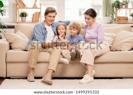 Young family of four relaxing on couch in living-room and watching movie or cartoons in digital tablet on weekend #1499295332
