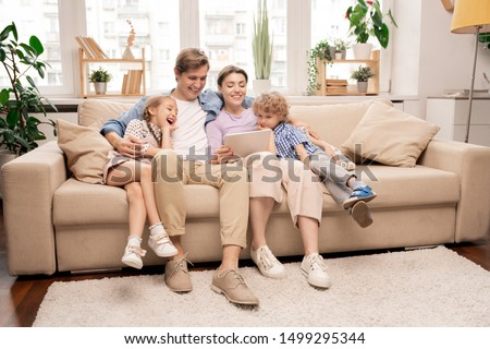 Cheerful kids and their parents in casualwear relaxing on couch in living-room and watching cartoons in tablet #1499295344