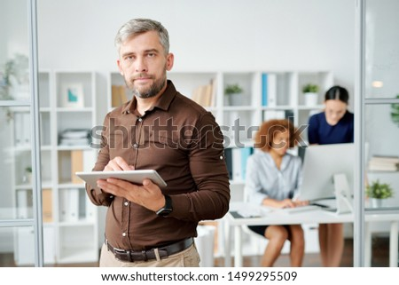 Serious businessman in smart casual looking at you in office environment while using tablet for network #1499295509