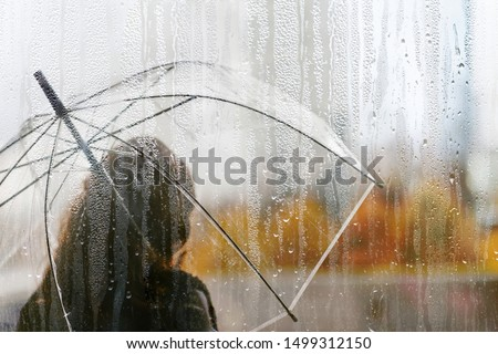A woman silhouette with transparent umbrella through wet window with drops of rain. Autumn #1499312150