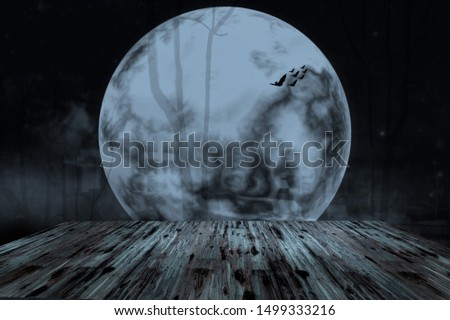 Halloween background. Spooky forest with dead trees and wooden table. Full moon night.