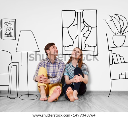 Young happy couple sitting on the floor in their new flat among painted furniture on the wall. #1499343764