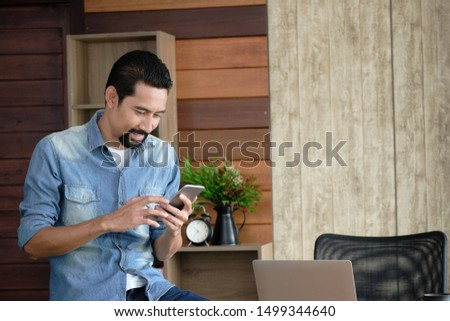 Handsome bearded guy is leaning on the desk and using the cellphone happily. Asian confident man sitting at the table in a private workspace while beautiful light shining through the window. #1499344640
