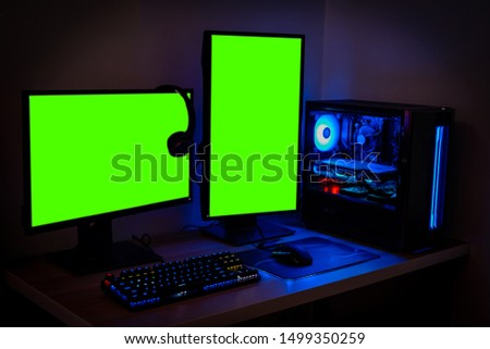 High-end PC Game Rig with dual Mock Up Green Screen or chroma key Monitor Stands. Modern Design is Lit with Blue and Neon Light. #1499350259