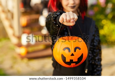 Closeup of unrecognizable little girl wearing Halloween costume and holding pumpkin basket in trick or treat season, copy space #1499358104