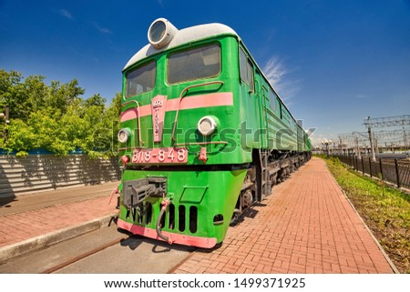 Old Soviet diesel locomotive on rails. Close-up on a background of blue sky on a summer sunny day #1499371925