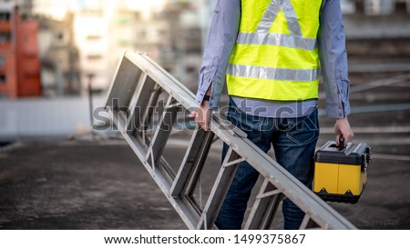 Maintenance worker man with safety helmet and green vest carrying aluminium step ladder and tool box at construction site. Civil engineering, Architecture builder and building service concepts #1499375867