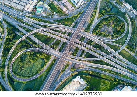 Aerial view of road interchange or highway intersection with busy urban traffic speeding on the road. Junction network of transportation taken by drone. Royalty-Free Stock Photo #1499375930