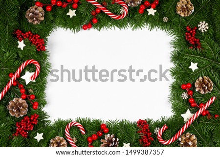 Christmas Border frame of tree branches around white background with copy space isolated, red decor, berries, stars, cones, candy canes