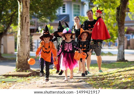 Child in Halloween costume. Mixed race Asian and Caucasian kids and parents trick or treat on street. Little boy and girl with pumpkin lantern and candy bucket. Baby in witch hat. Autumn holiday fun. #1499421917