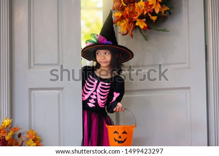 Kids trick or treat on Halloween. Little Asian girl at decorated house door with autumn leaf wreath and pumpkin lantern. Child in witch and skeleton costume and hat with candy bucket. Fall decoration. #1499423297