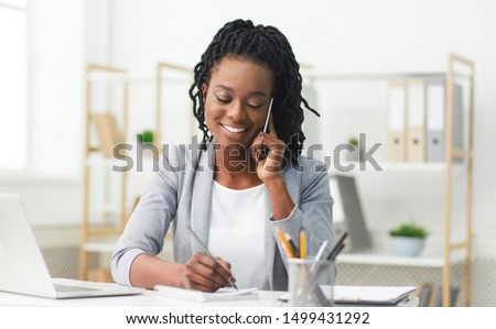 Black Businesswoman Having Phone Conversation Taking Notes In Modern Office. Copy Space #1499431292