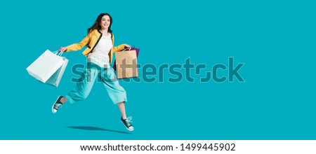 Cheerful happy woman enjoying shopping: she is carrying shopping bags and running to get the latest offers at the shopping center #1499445902