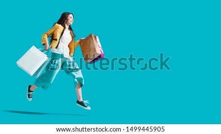 Cheerful happy woman enjoying shopping: she is carrying shopping bags and running to get the latest offers at the shopping center #1499445905