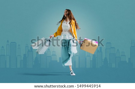 Cheerful happy girl shopping and walking in the city street holding a lot of shopping bags #1499445914