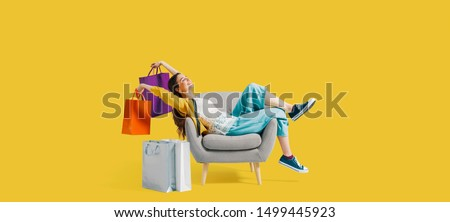 Cheerful happy shopaholic woman with lots of shopping bags, she is sitting on an armchair and celebrating, blank copy space Royalty-Free Stock Photo #1499445923
