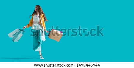 Cheerful young woman enjoying shopping: she is walking and swinging her shopping bags, sales and fashion concept #1499445944