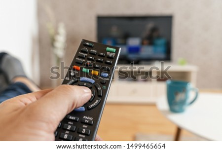 man with the remote control in hand watching the smart tv and presses the button on the remote control. Remote control in hand closeup. #1499465654