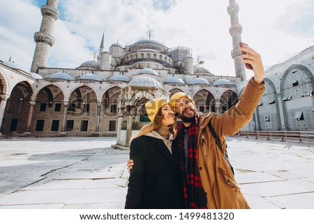 A young European couple walks in the courtyard of the Blue Mosque and takes a selfie, Istanbul Turkey. Traveler guy and girl in yellow hats are photographed in winter Istanbul. #1499481320