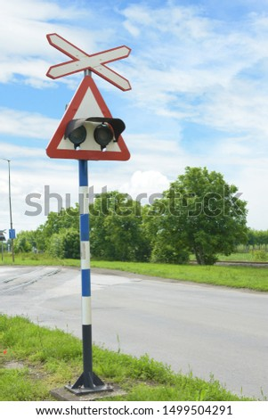 Vertical image of Saint Andrews Cross or cross buck with lights it is a sign for level crossing intersection where a railway line crosses a road or path on a nice sunny day #1499504291