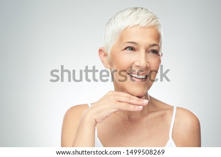 Beautiful smiling senior woman with short gray hair posing in front of gray background. Beauty photography. #1499508269