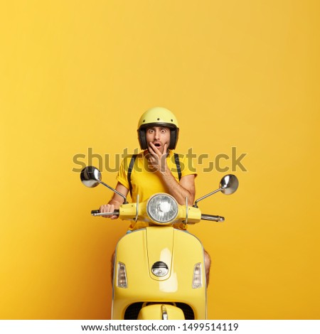 Vertical shot of scared young man stares at camera with frightened face expression, wears yellow protective helmet, t shirt, drives fast motorbike, delivers something for customers, poses indoor #1499514119