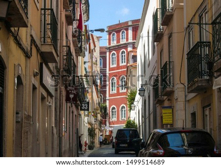 Lisbon/Portugal - July 17th 2018: Old narrow street with shops and cars on a sunny day, downtown.  #1499514689
