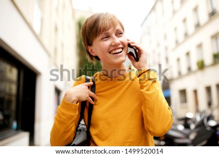 Portrait of young woman with handbag walking in the city and talking with cellphone #1499520014