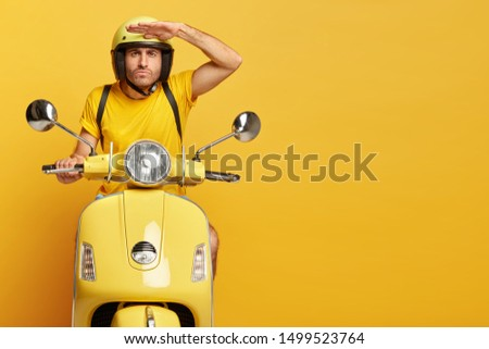 Concentrated male driver in helmet on scooter, keeps palm near forehead, poses on motorbike, carries rucksack, has serious face expression, poses against yellow background, copy space on right side #1499523764