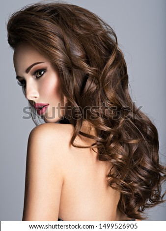 Beautiful woman with long bown hair. Profile Portrait of an sensual adult girl with curly hair. #1499526905