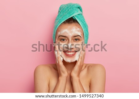 Positive young female has toothy smile, has perfect teeth, pats skin with liquid sanitary soap, washes with foaming gel, wakes up in morning for having beauty routine, isolated on pink background #1499527340