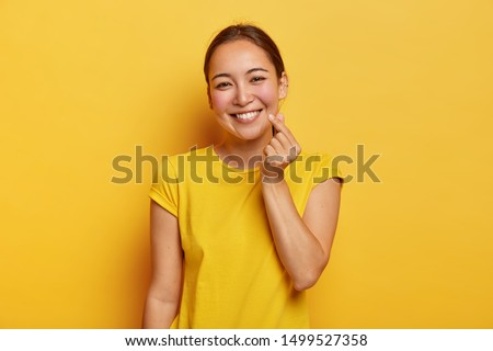 Happy lady with Asian appearance makes korean like sign, dressed in casual yellow t shirt has friendly face expression stands indoor. Monochrome shot. Body language. Female expresses love with gesture #1499527358