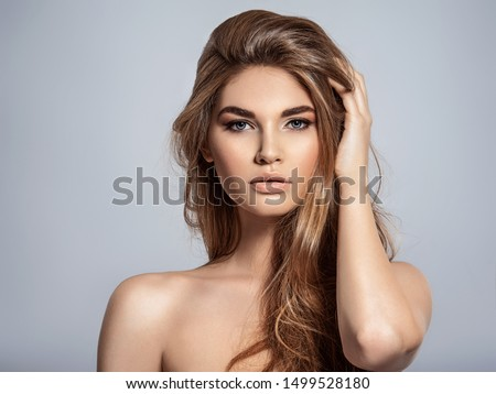 Woman with beauty long brown hair and natural makeup.  Beautiful face of an attractive  model with blue eyes. Closeup portrait of a caucasian female. Attractive fashion model. #1499528180