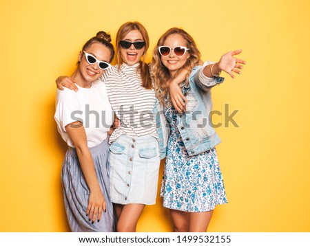 Three young beautiful smiling hipster girls in trendy summer clothes. Sexy carefree women posing near yellow wall in studio. Positive models going crazy and having fun. In sunglasses #1499532155