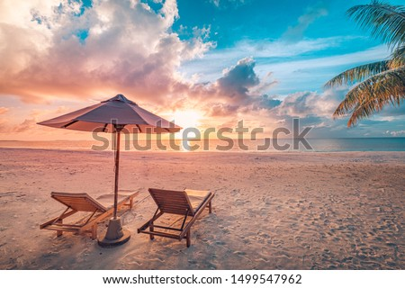 Beautiful tropical sunset scenery, two sun beds, loungers, umbrella under palm tree. White sand, sea view with horizon, colorful twilight sky, calmness and relaxation. Inspirational beach resort hotel