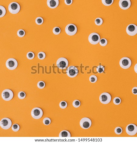 Halloween monster eyes orange background. Funny holiday flat lay concept.