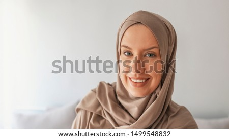 Portrait of beautiful young muslim arabian woman wearing hijab looking at camera, copy space. Girl in hijab. Portrait of a young woman eastern type in the modern Muslim clothes and beautiful headdress #1499548832