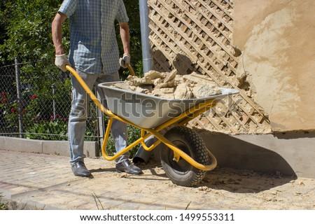 to carry wheelbarrow construction debris,a man with a wheelbarrow debris near the house #1499553311