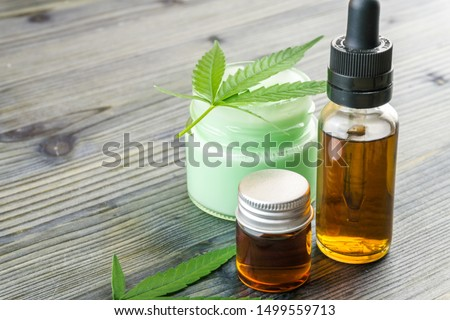 Cannabis CBD oils in glass bottle and CBD lotion gel little jars with hemp leafs on wooden table #1499559713