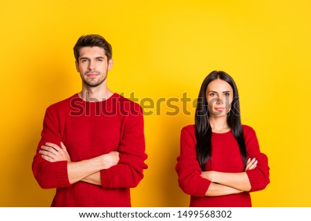 Portrait of concentrated couple with crossed hands wear red jumper isolated over yellow background #1499568302
