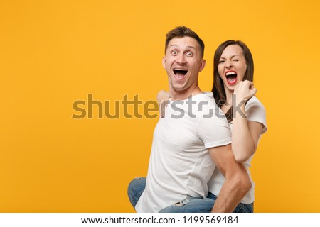 Excited young couple in white t-shirts posing isolated on yellow orange background. People lifestyle concept. Mock up copy space. Giving piggyback ride to joyful sitting on back, doing winner gesture #1499569484